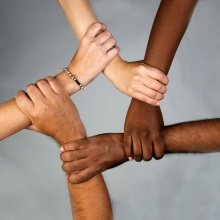 5 hands from people of different races holding each other's wrist